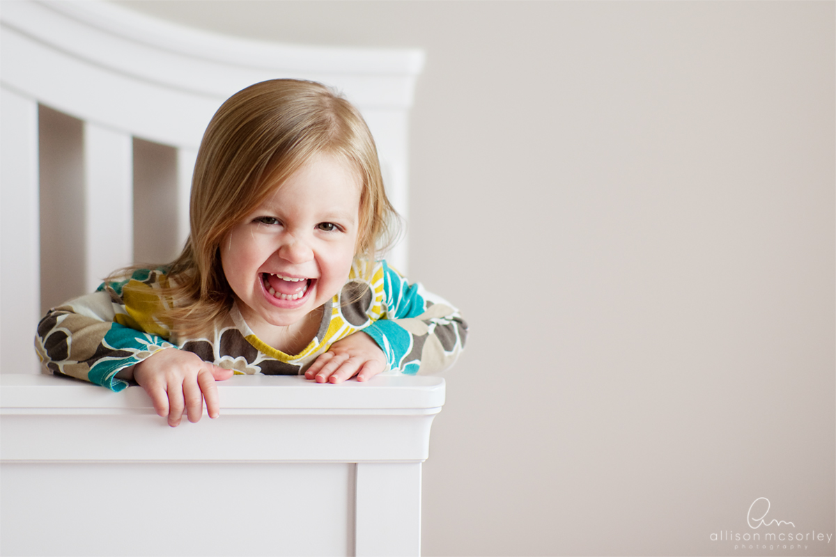 toddler laughing in her crib by Allison McSorley