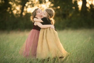 two girls hugging in a field by Sally Kate Photography