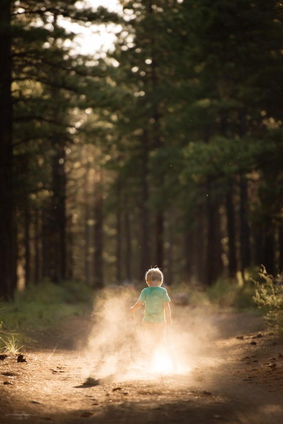 backlit photo of boy walking in the dirt by Lacey Meyers