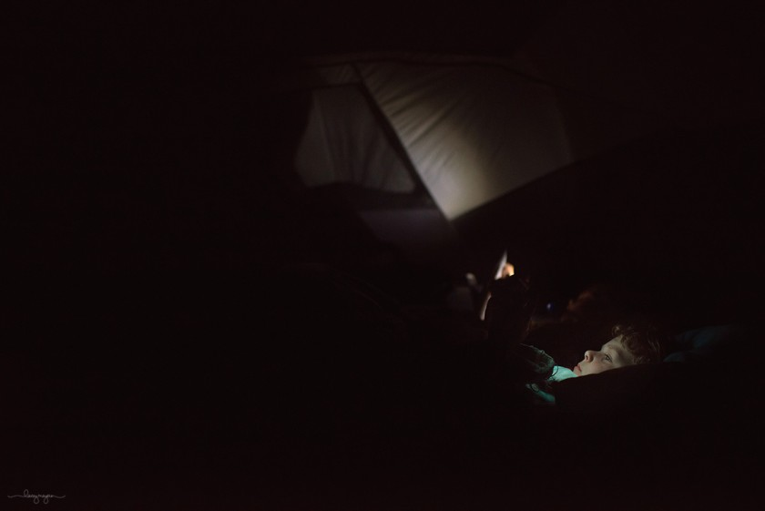 boy laying in his camping tent at night by Lacey Meyers