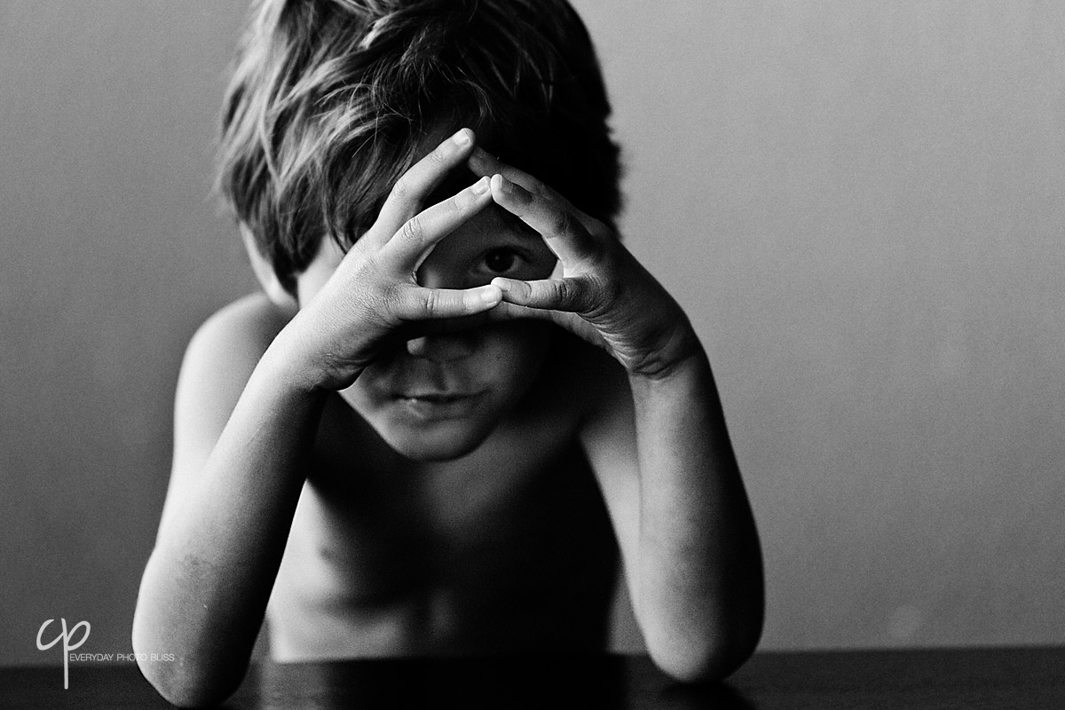 boy looking through fingers by Celeste Pavlik