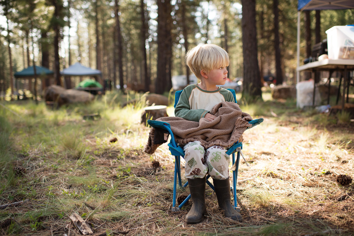 boy sitting in a lawn chair while camping by Lacey Meyers