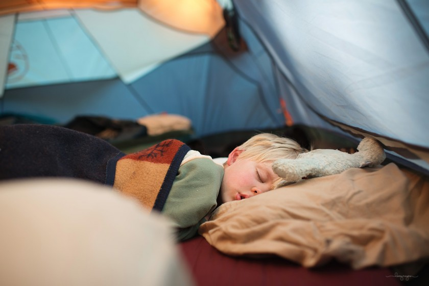 boy sleeping in a tent by Lacey Meyers