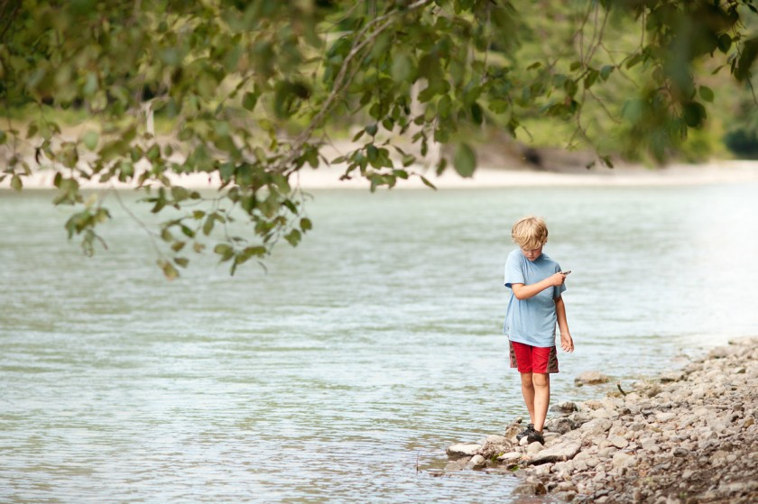 boy walking along the river by Lacey Meyers