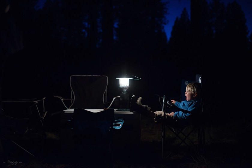 boy yawning while camping by Lacey Meyers