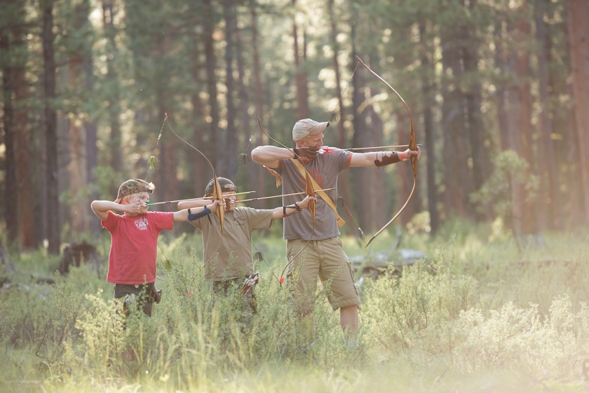 dad and sons shooting bows by Lacey Meyers