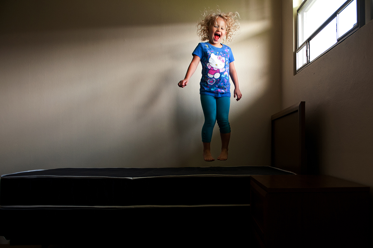 girl jumping on a bed by Meredith Novario