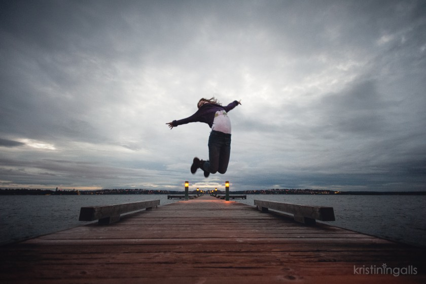 girl jumping on a dock by Kristin Ingalls