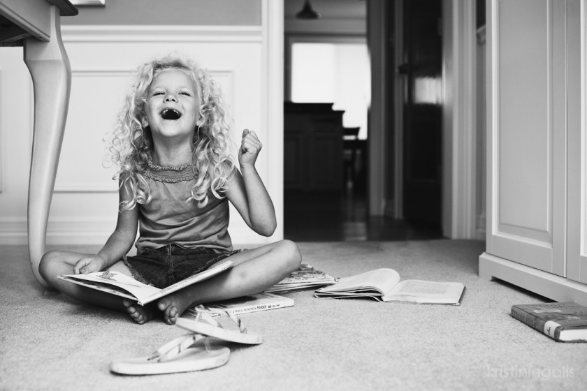 girl laughing and reading books by Kristin Ingalls