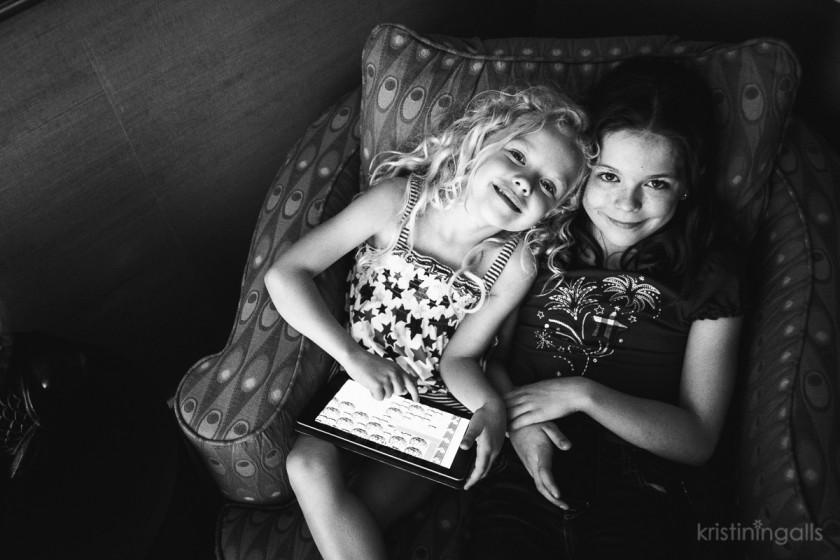 girls playing on an ipad by Kristin Ingalls