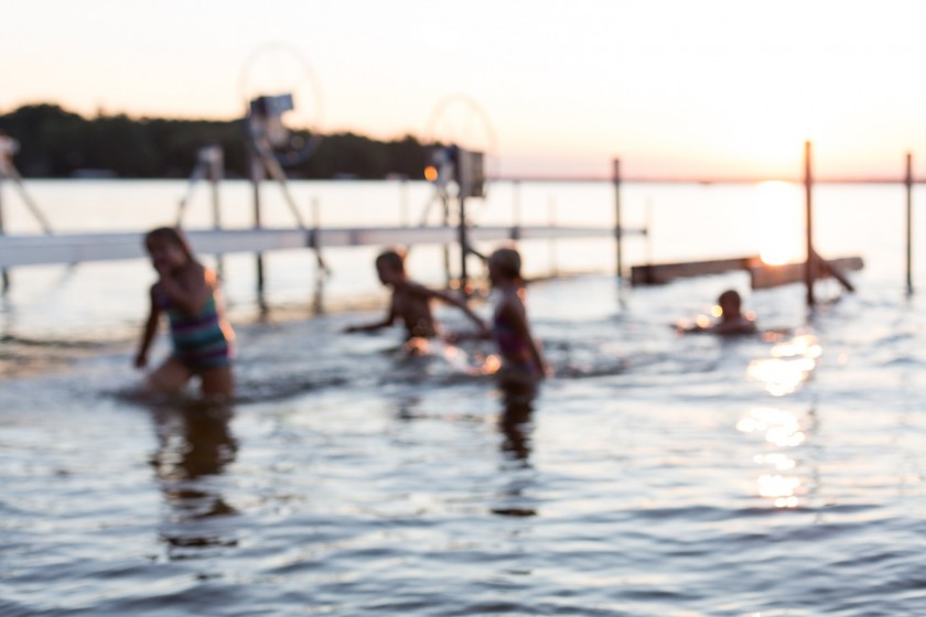 out-of-focus-kids-in-water-near-dock-during-sunset-by-hdbb