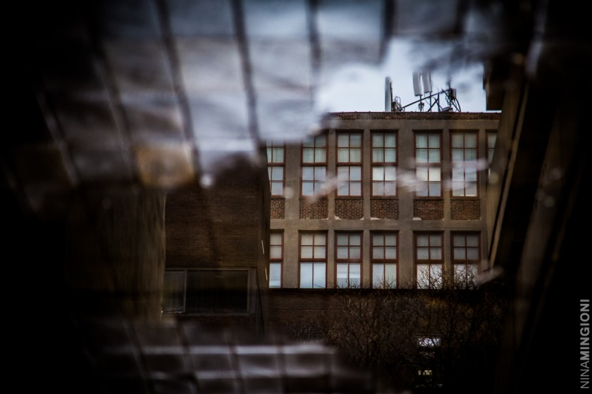 puddle with city building reflected by Nina Mingioni