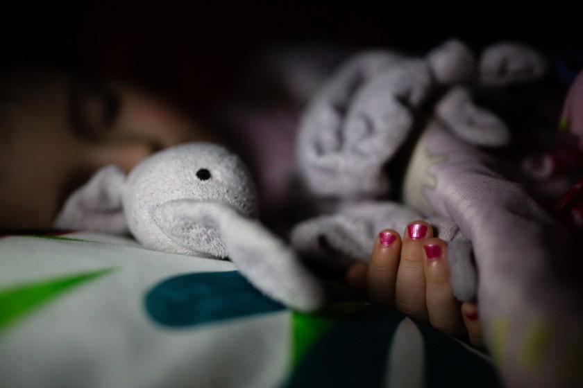 sleeping girl holding stuffed bunny by Kristy Dooley