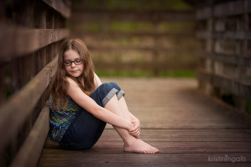 young girl sitting on a wooden path by Kristin Ingalls
