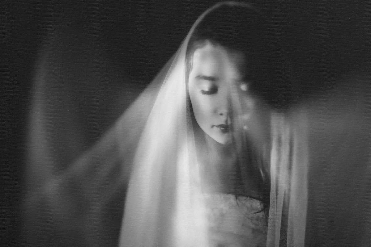 black and white photo of girl with curtains by Caroline Jensen