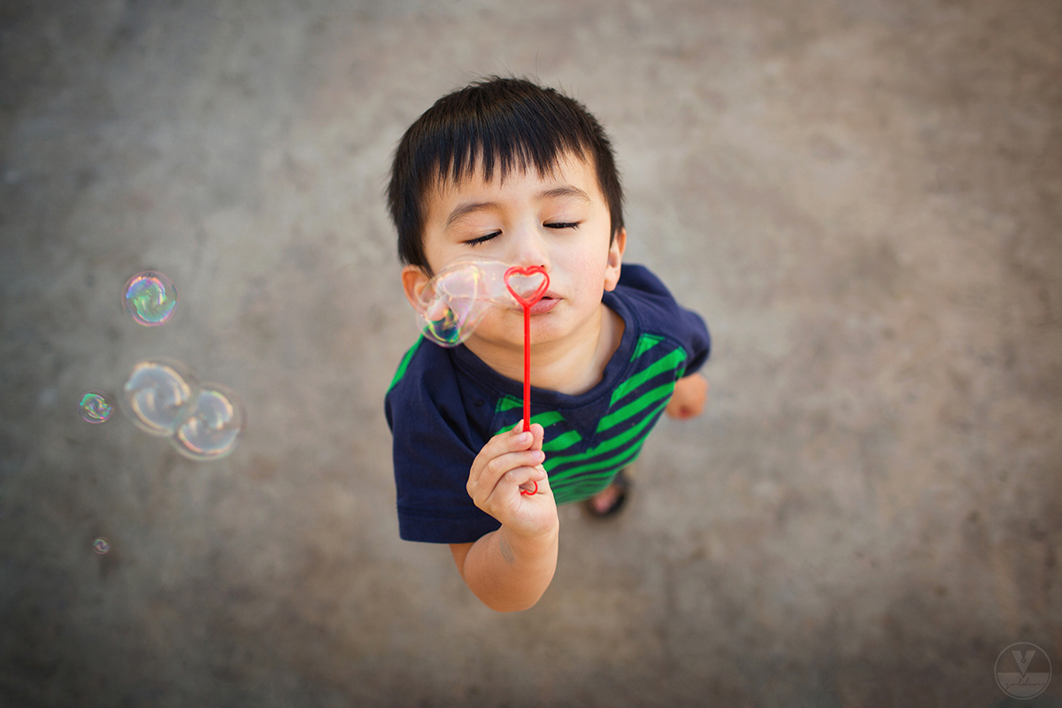 boy blowing heart bubbles by Vironica Golden