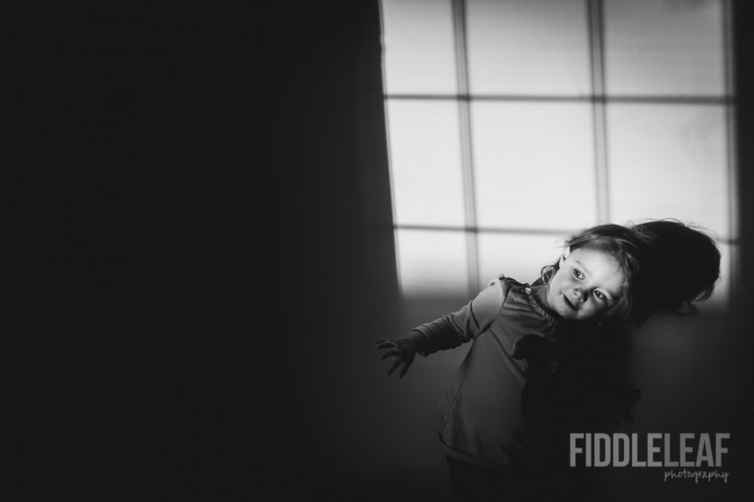 child playing in the light and shadows by Kelly Marleau of Fiddle Leaf Photography