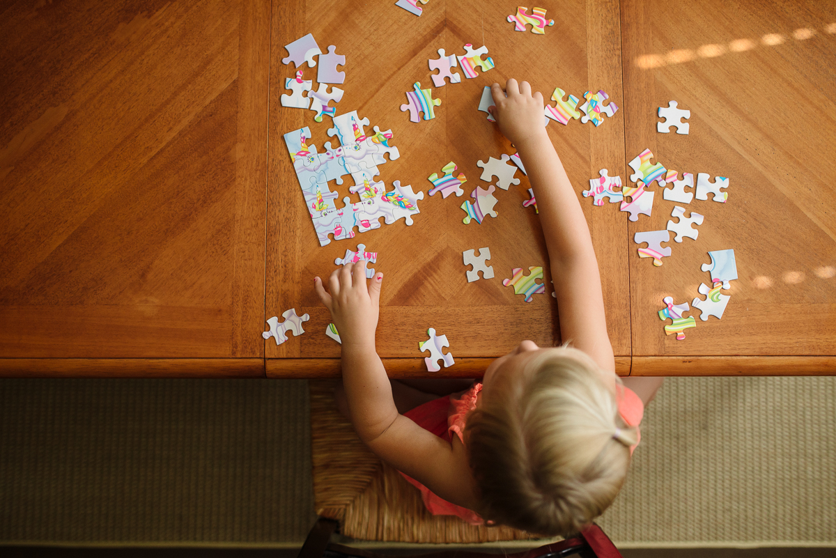 child putting a puzzle together by Sarah Carlson