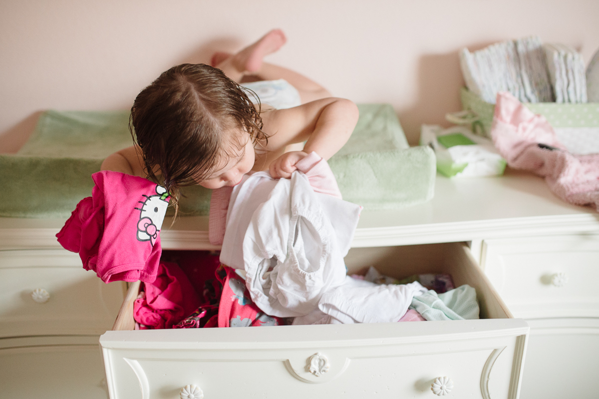 girl getting clothes out of her dresser by Sarah Carlson