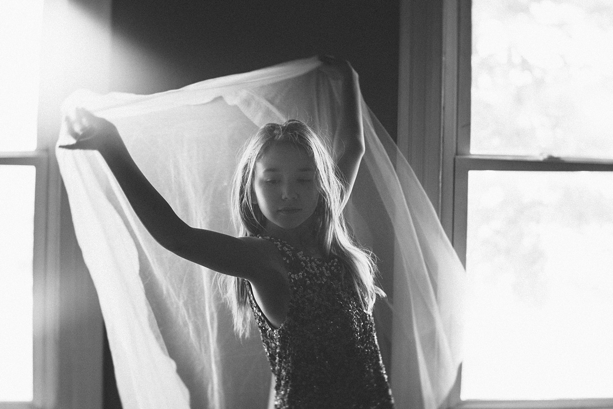 girl holding curtains by Caroline Jensen