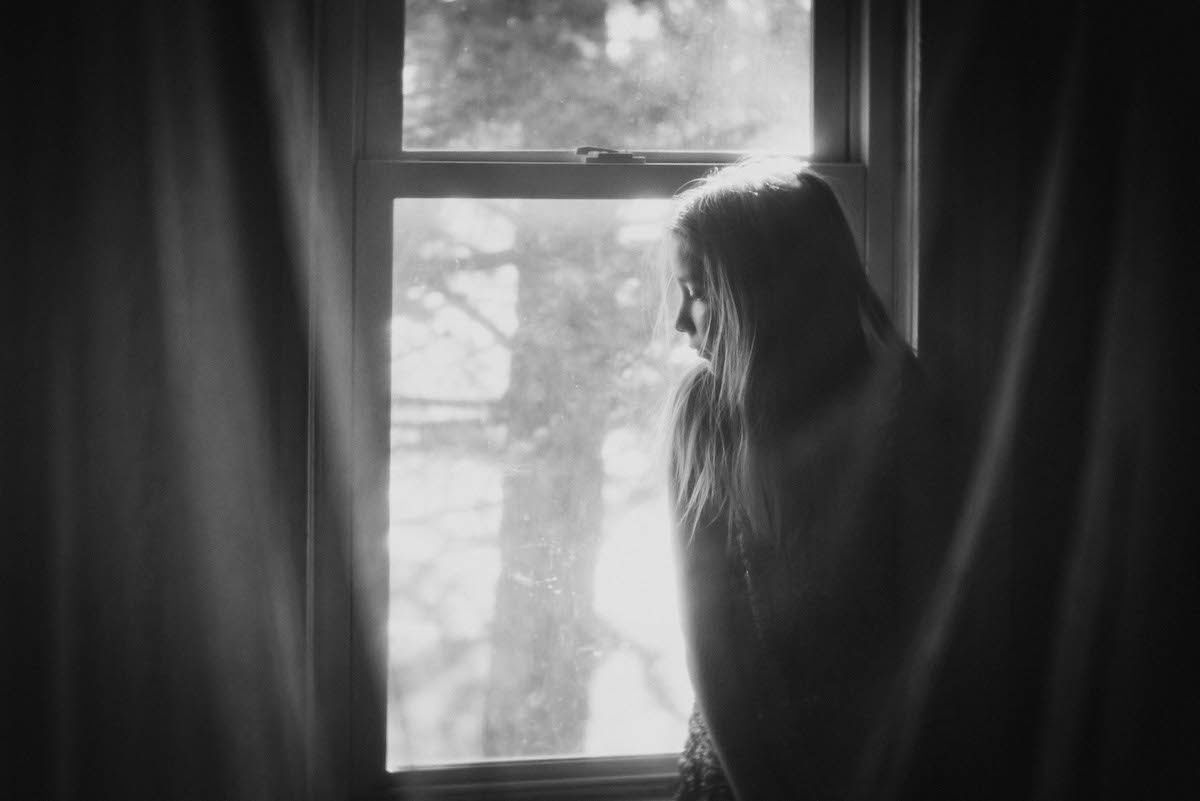 girl sitting in front of window by Caroline Jensen