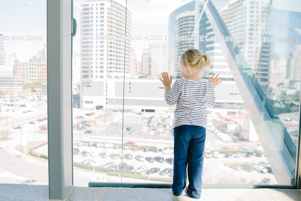 girl standing in window and looking at the skyline by Sarah Carlson