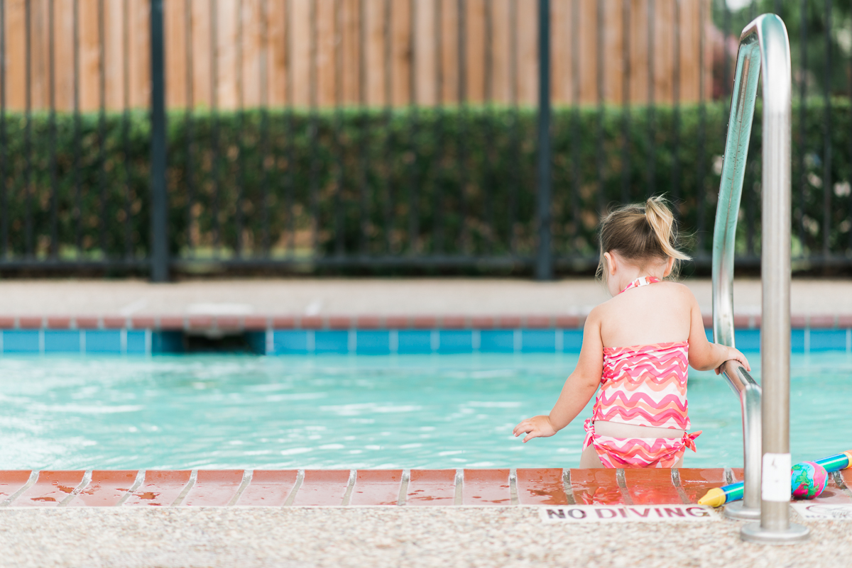 girl stepping into the swimming pool by Sarah Carlson