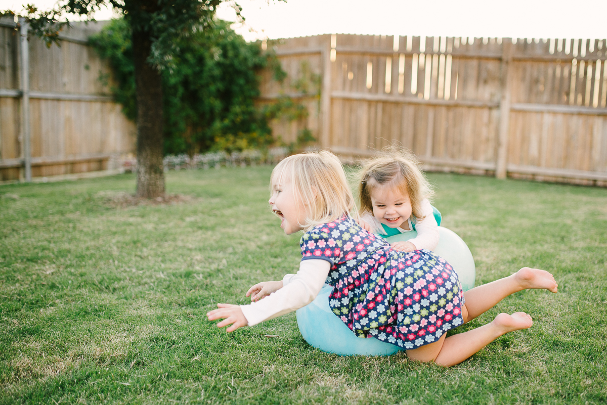 girls rolling outside on a big ball by Sarah Carlson