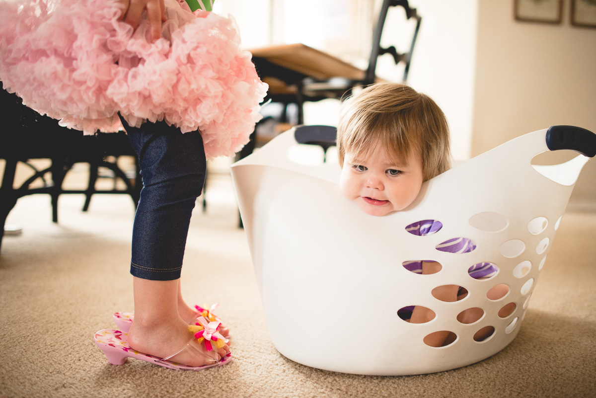 kid in a laundry basket by Sarah Carlson