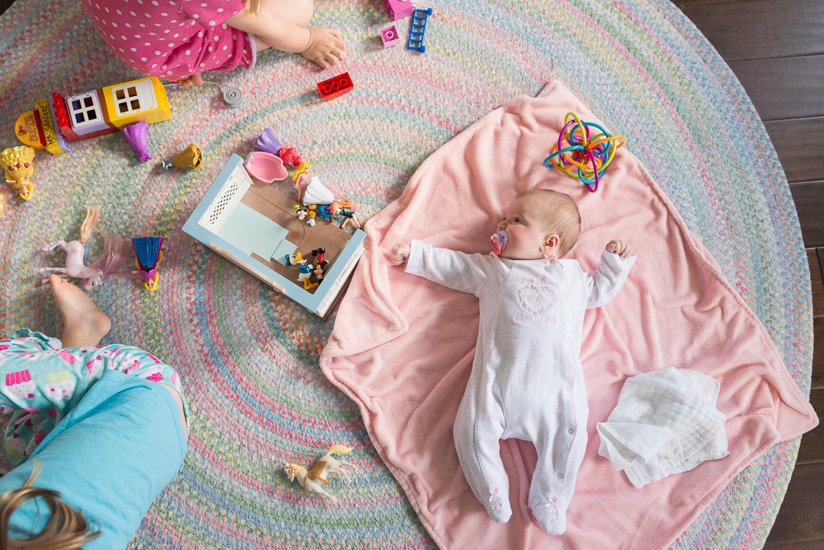 sisters playing on the floor by Sarah Carlson
