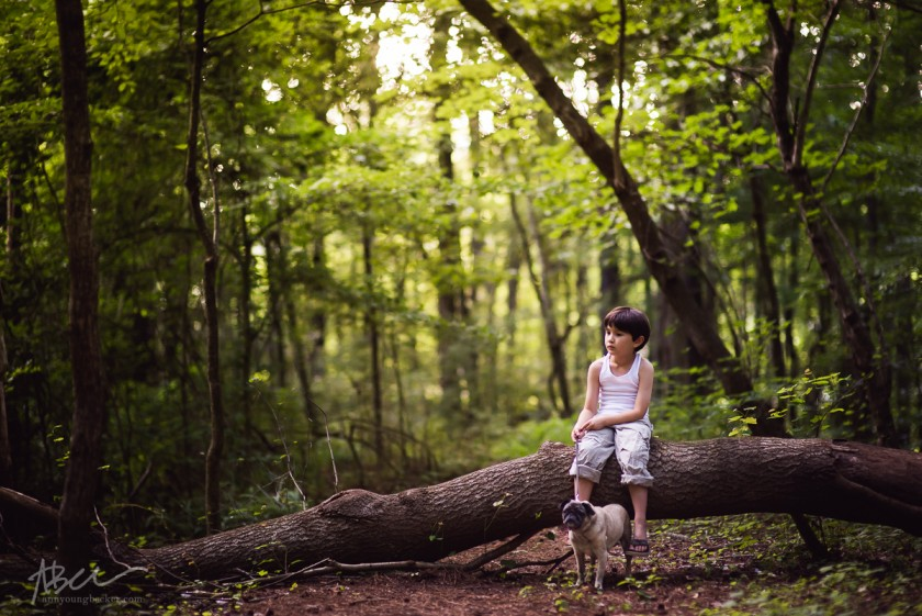 child sitting on a log in the woods by Ann Becker