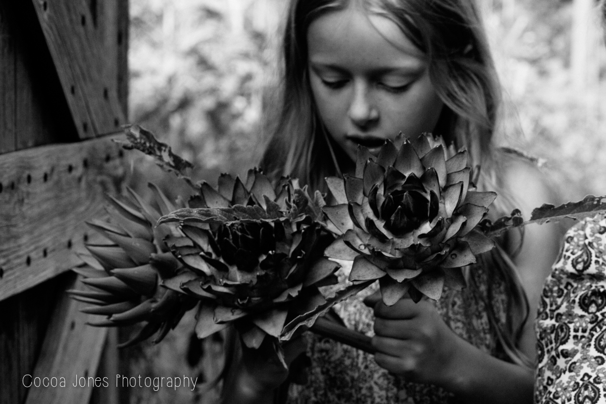 girl holding flowers by Thea Courtney of Cocoa Jones Photography