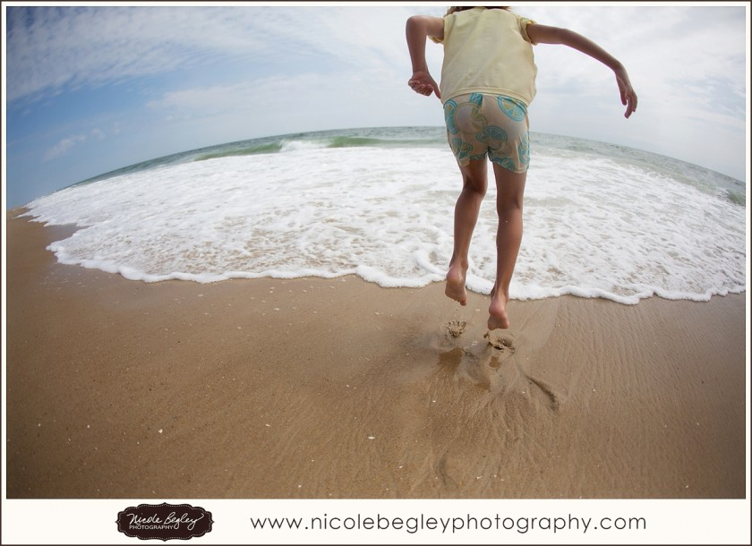 girl jumping on the beach by Nicole Begley
