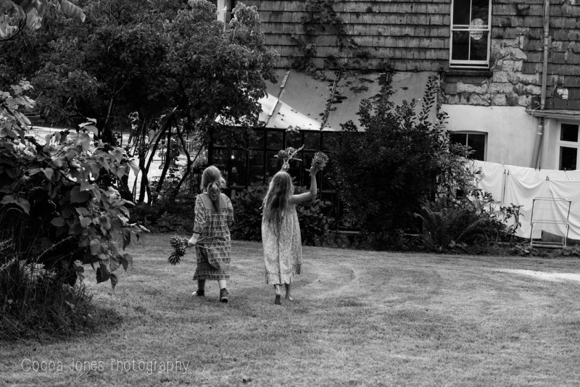girls walking through the yard by Thea Courtney of Cocoa Jones Photography