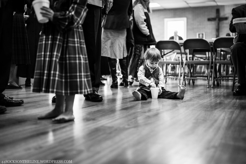 kid playing on the floor with a cup by Sarah Hodges
