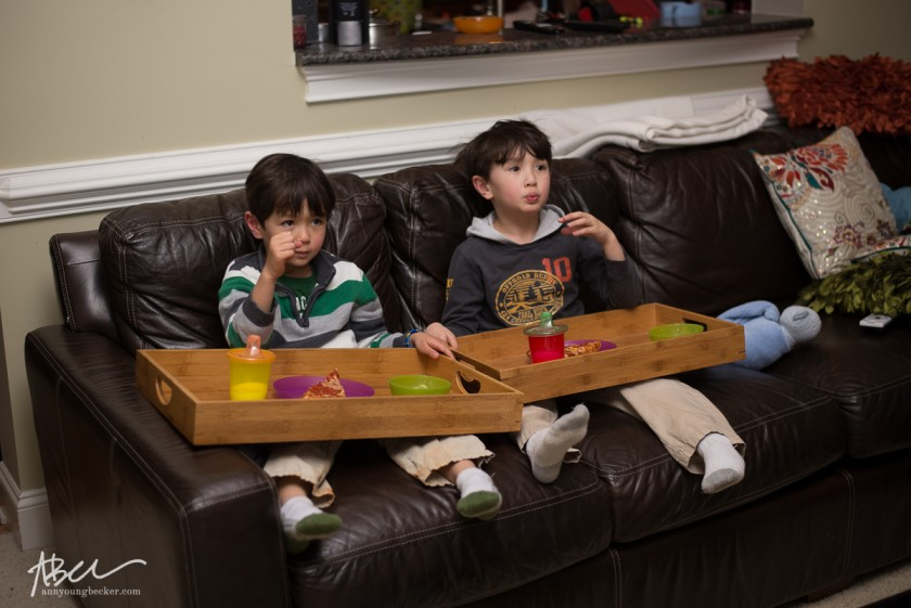 kids eating on the couch by Ann Becker