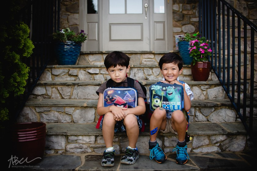 kids sitting on the steps holding their lunchboxes by Ann Becker