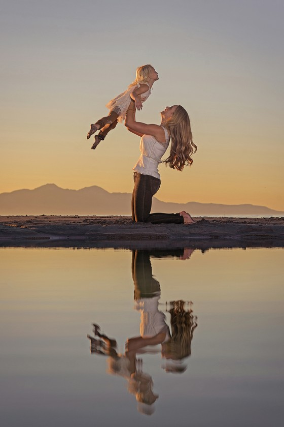 mom lifting daughter with reflection in the water by Michelle Turner
