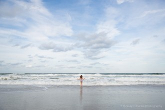 photo of girl standing in front of the ocean by Lindsay Moeser