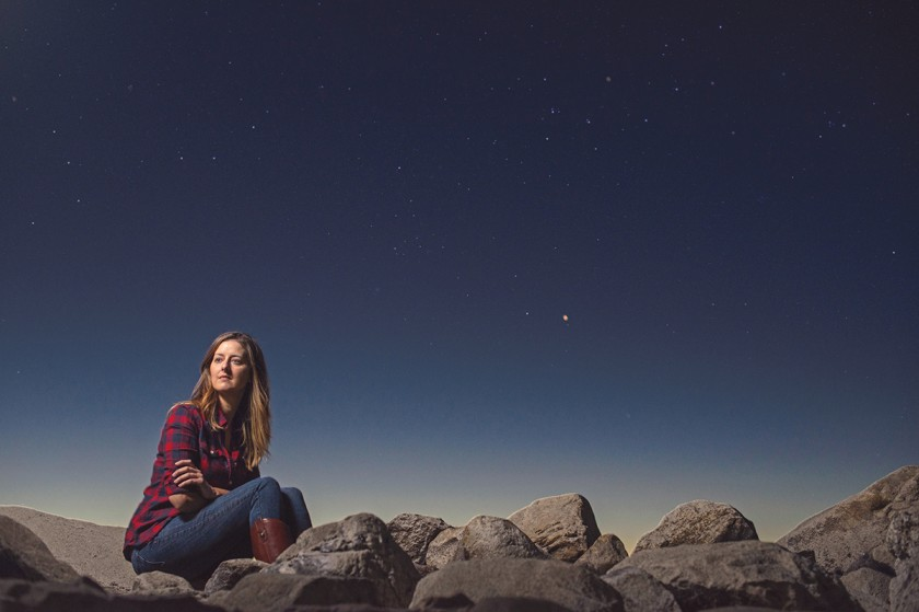woman sitting on rocks with the stars by Michelle Turner