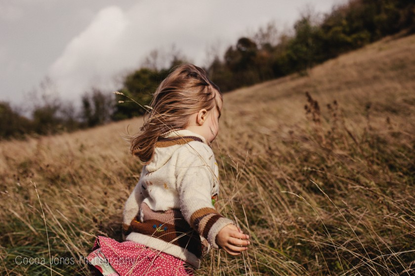 young girl in a field by Thea Courtney of Cocoa Jones Photography