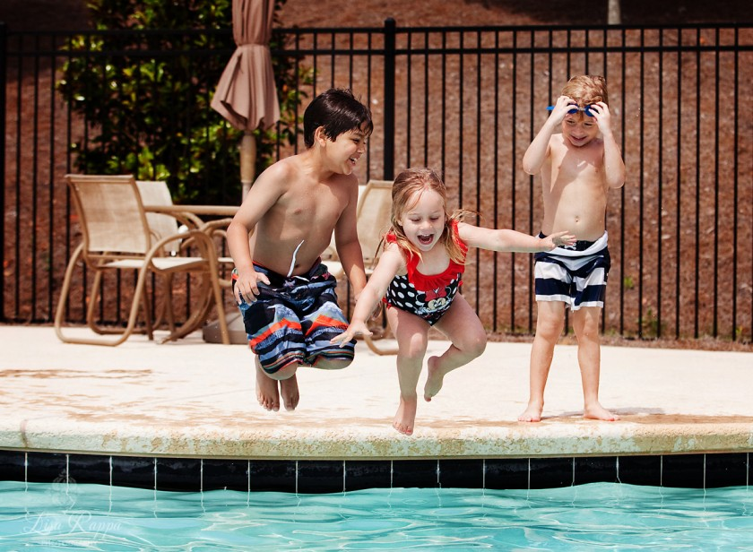 3 kids jumping in the swimming pool by Lisa Rappa
