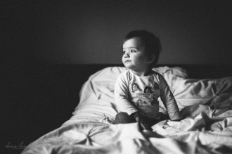 baby sitting on a bed by Dana Lauder