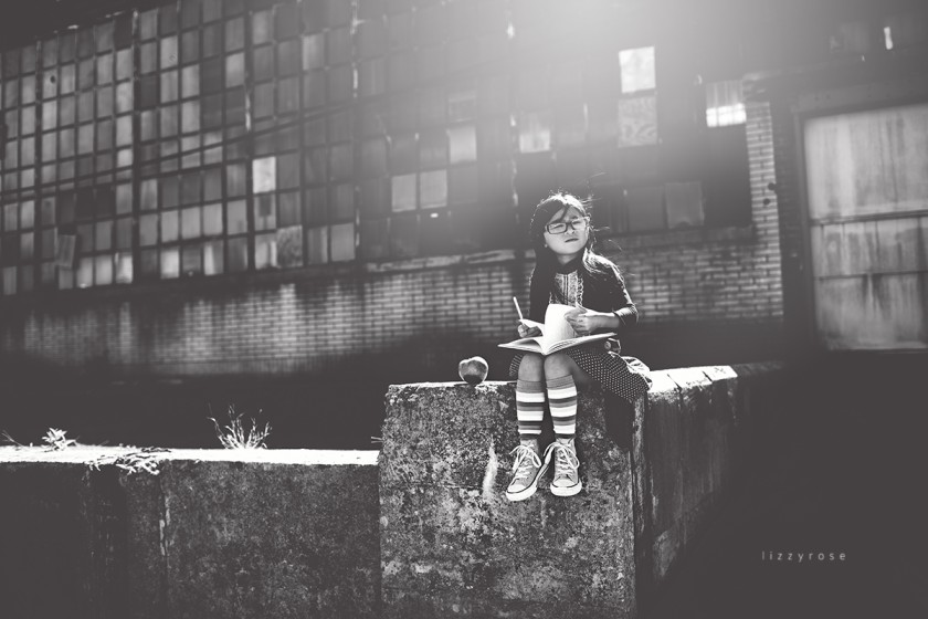 child sitting on a ledge by Lisa Furey