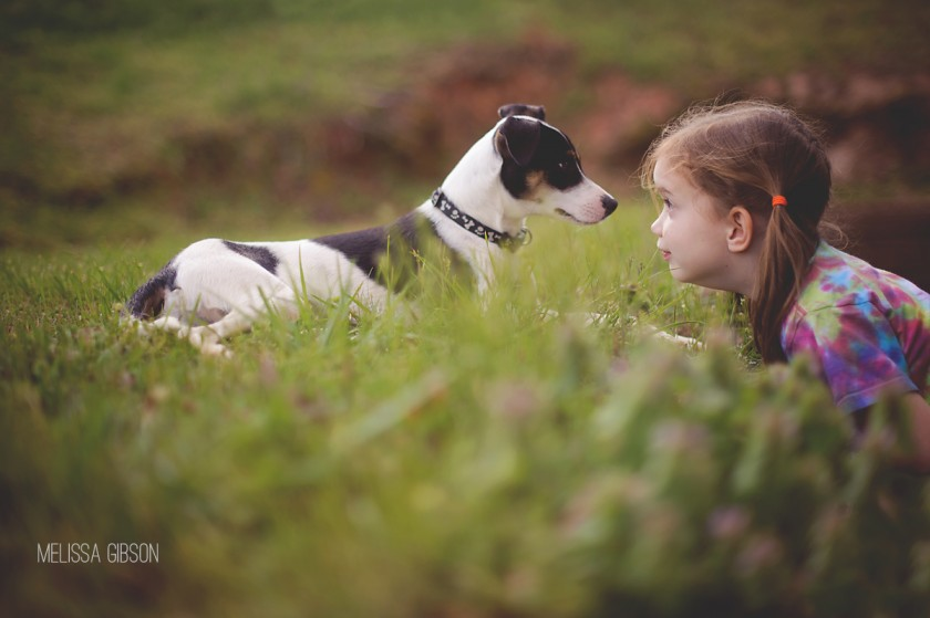 girl and dog staring at each other by Melissa Gibson
