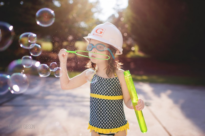 girl blowing bubbles with a hard hat on by Melissa Gibson