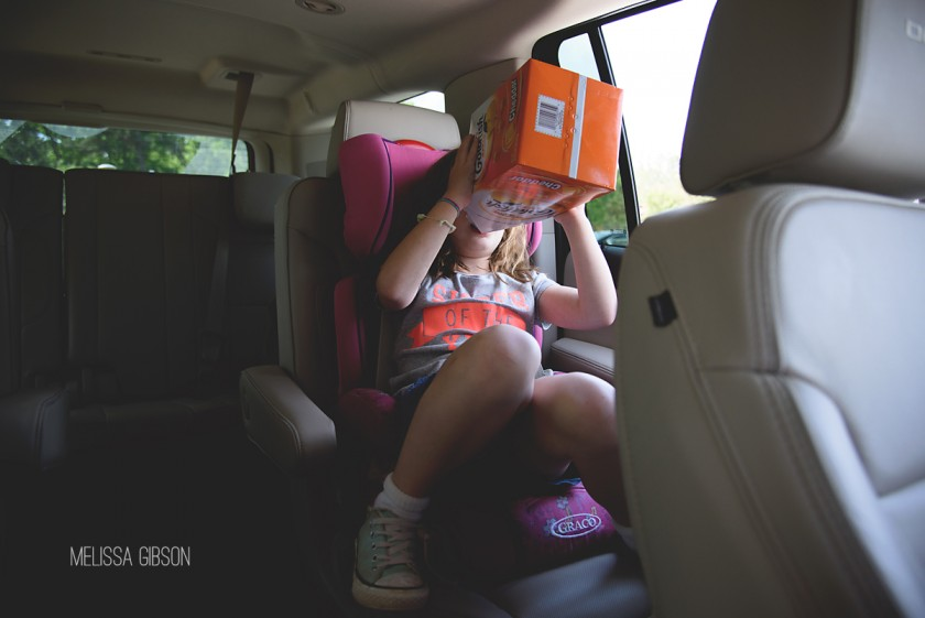 girl eating a box of goldfish in the car by Melissa Gibson