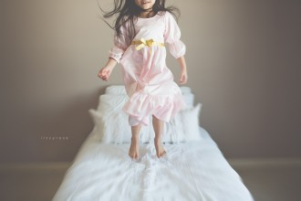 girl jumping on a bed by Lisa Furey