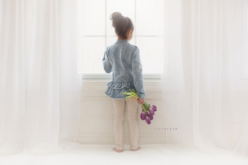 girl looking out a window holding tulips by Lisa Furey