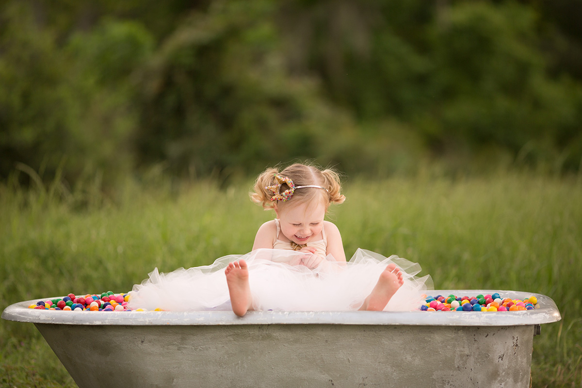 girl sitting in a bathtub full of bubble gum by Shalonda Chaddock of Chubby Cheek Photography